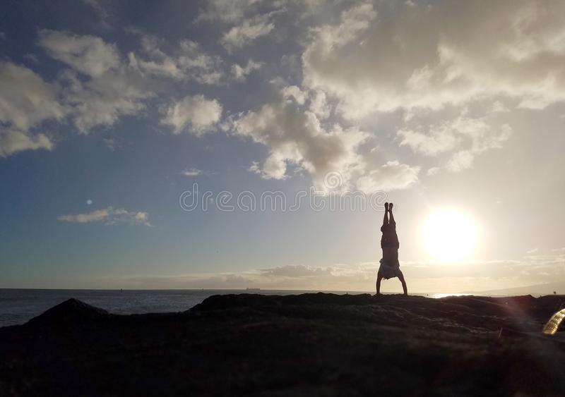 Mens Handstanding op kustrotsen bij zonsondergang stock afbeeldingen