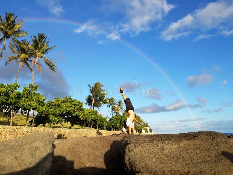 Mens Handstanding op kustrotsen met Regenboog lucht stock foto's