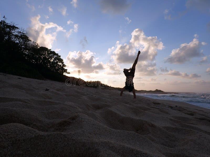 Mens Handstanding op strand bij zonsondergang als golfneerstorting royalty-vrije stock foto's