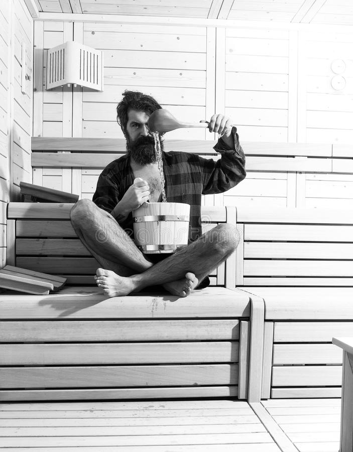 Mens heals body care. handsome bearded man in wooden bath with bucket and spoon. Mens heals body care. handsome bearded man or guy barefoot in checkered red stock photo