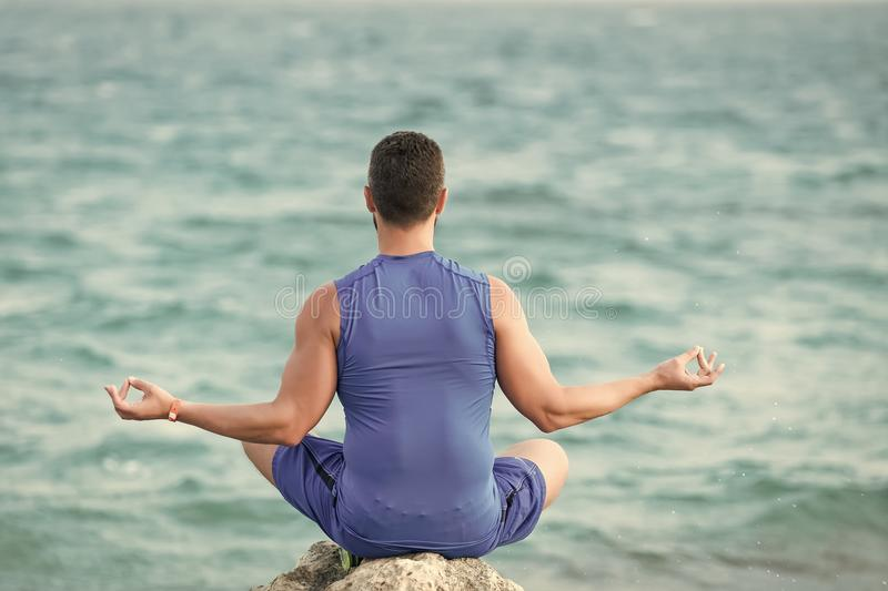 Mens heals body care. yogi having meditation at beach. Health and fitness concept. boy practicing yoga asana alone. yoga and meditation. yoga at coast of blue royalty free stock photos