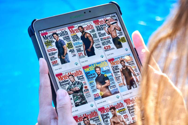 Mens Health magazine on a Samsung Galaxy tablet screen. MONTREAL, CANADA - SEPTEMBER 8, 2018: Mens Health magazines on a Samsung Galaxy tablet in hands royalty free stock images