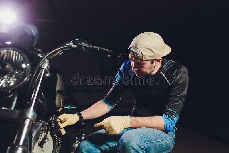 Mens het bevestigen fiets Zekere jonge mens die motorfiets herstellen dichtbij zijn garage royalty-vrije stock foto's