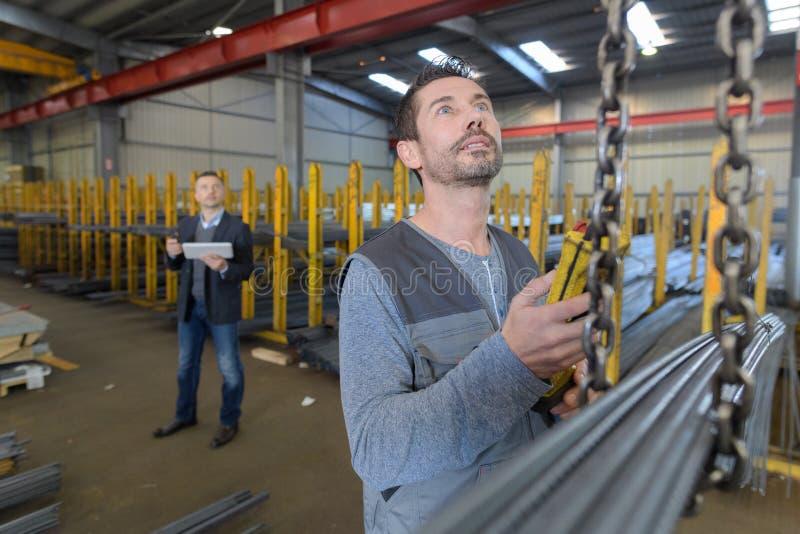 Mens het controleren hijstoestel in fabriek stock afbeeldingen