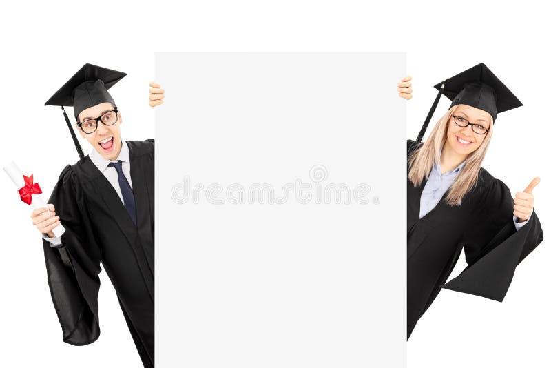 Mens in het diploma van de togaholding en meisje die duim opgeven stock afbeelding