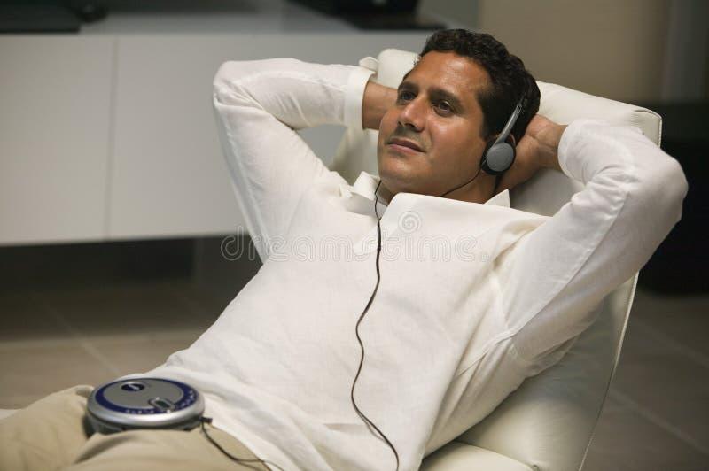 Mens het Doen leunen in woonkamer die aan draagbare CD speler luisteren royalty-vrije stock foto