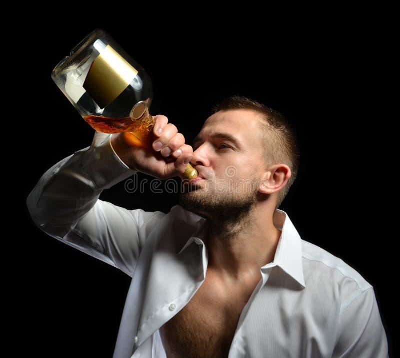 Mens het drinken de whisky van de cognacalcohol van de fles royalty-vrije stock afbeeldingen