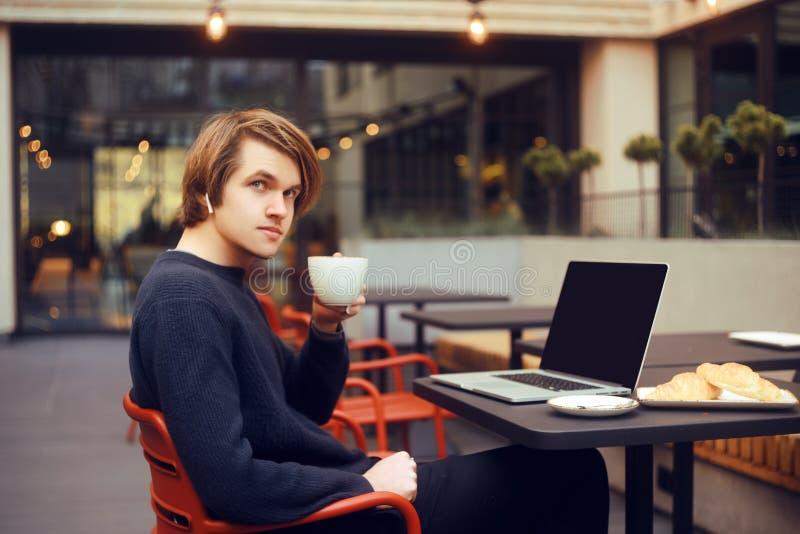 Mens het drinken koffie in een restaurant op het terras Freelancer openlucht met laptop, heeft ontbijt met croissants jong royalty-vrije stock afbeelding