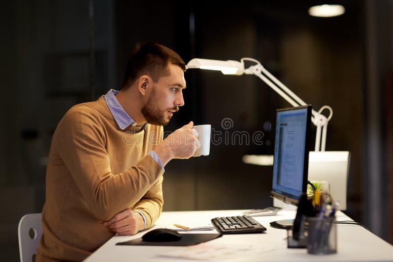 Mens het drinken koffie en het werken aan code op kantoor stock foto