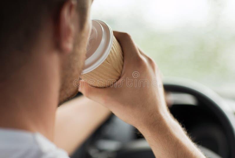 Mens het drinken koffie terwijl het drijven van de auto stock foto's