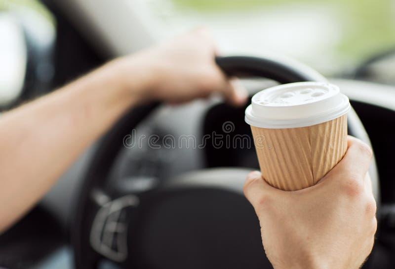 Mens het drinken koffie terwijl het drijven van de auto stock foto
