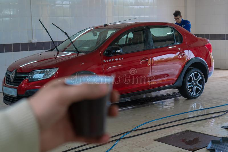 Mens het drinken koffie terwijl het wachten op zijn te wassen auto Schone machine, autowasserette met spons en slang Renault Loga stock afbeeldingen