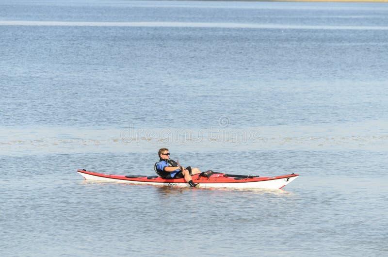 Mens het floting op de rivier in zijn kano stock fotografie
