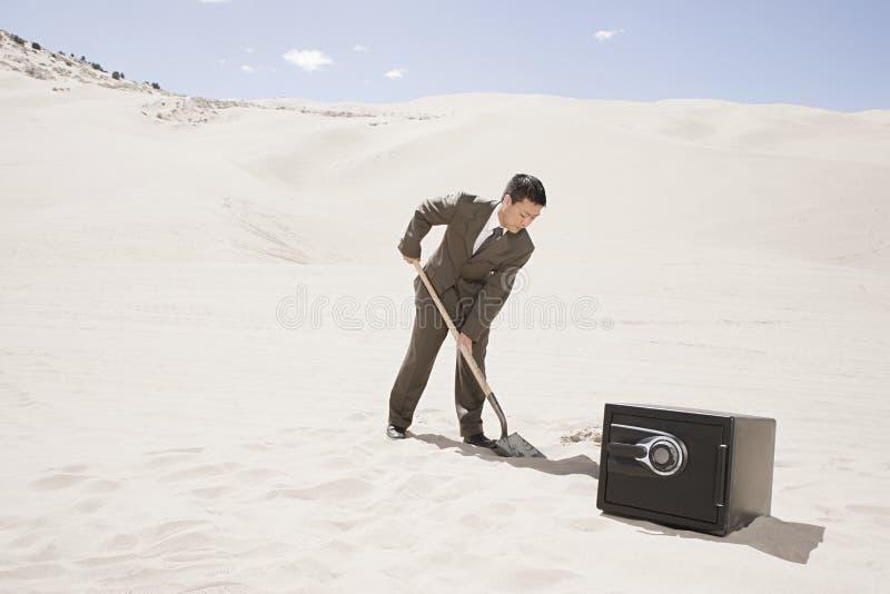 Mens het graven door brandkast in woestijn royalty-vrije stock foto