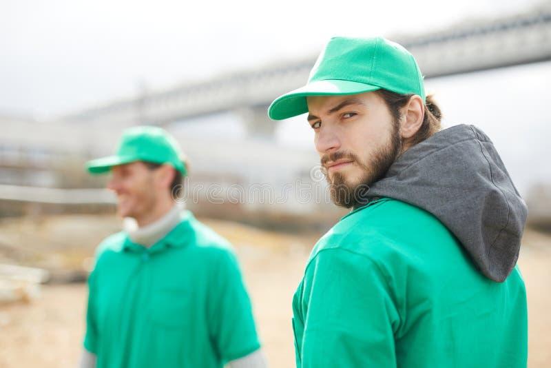 Mens in het groene eenvormige bekijken camera stock afbeelding