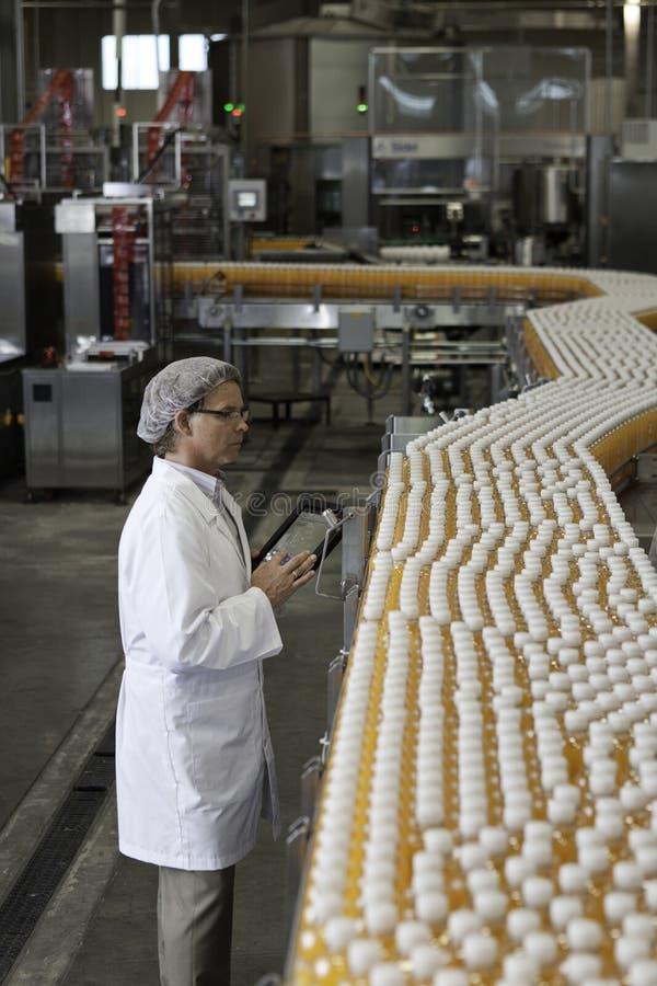 Mens het inspecteren jus d'orangeflessen bij bottelarij stock afbeeldingen