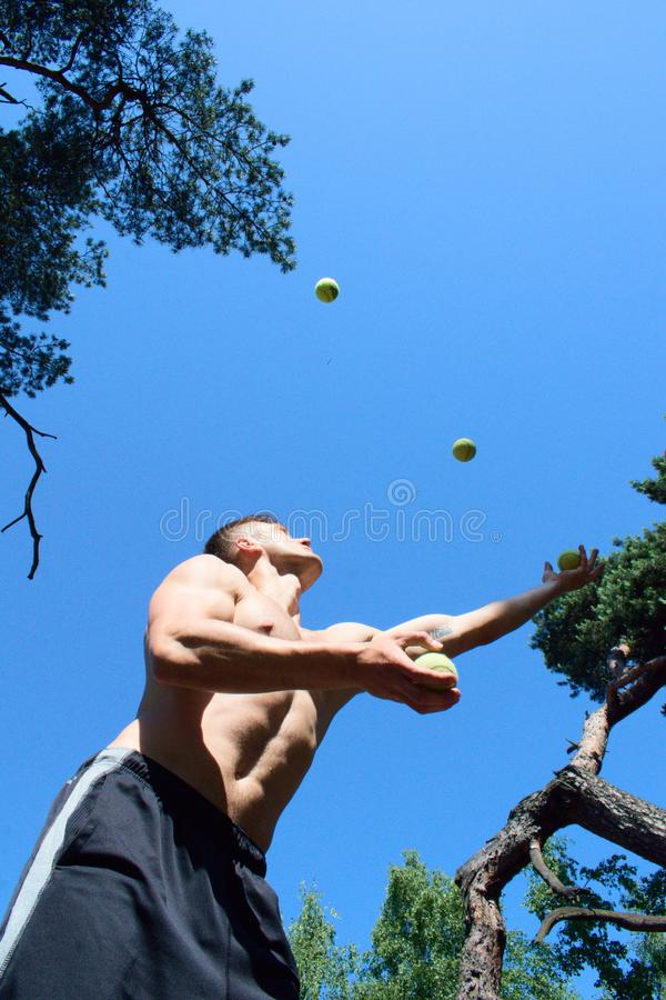 Mens het jongleren met met ballen bij het park stock afbeelding