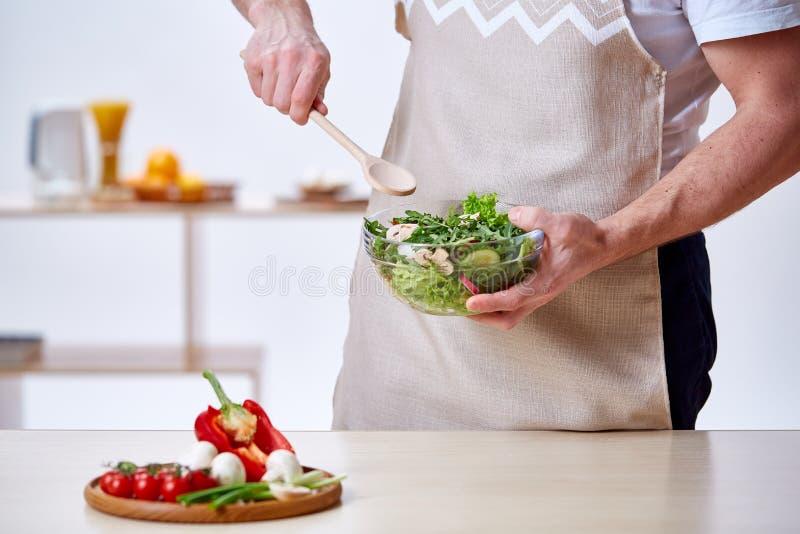Mens het koken bij keuken die gezonde plantaardige salade, close-up, selectieve nadruk maken stock afbeeldingen