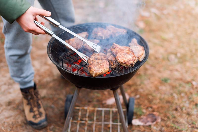 Mens het koken, slechts handen, roostert hij vlees of lapje vlees voor een schotel Heerlijk Geroosterd Vlees bij de Grill Barbecu royalty-vrije stock afbeeldingen