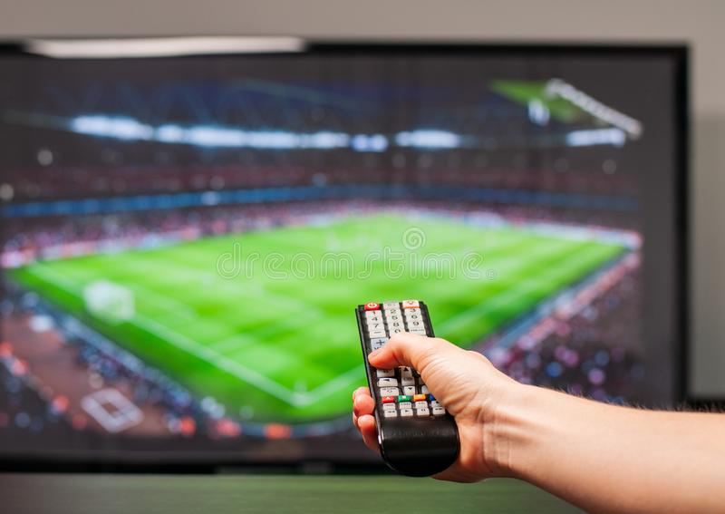 Mens het letten op voetbalwedstrijd op televisie, de afstandsbediening ter beschikking stock fotografie