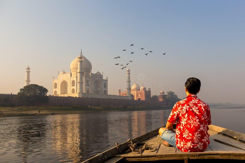 Mens het letten op zonsondergang over Taj Mahal van een houten boot met vogel die over vliegen stock afbeelding
