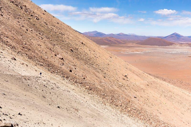 Mens het lopen de sleep Salar De Uyuni, Bolivië van de vulkaanberg stock afbeelding