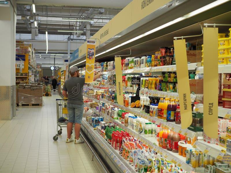 Mens het maken choise van plank in supermarkt Het concept van het consumentisme Rusland, Saratov - 28 April 2019 stock fotografie
