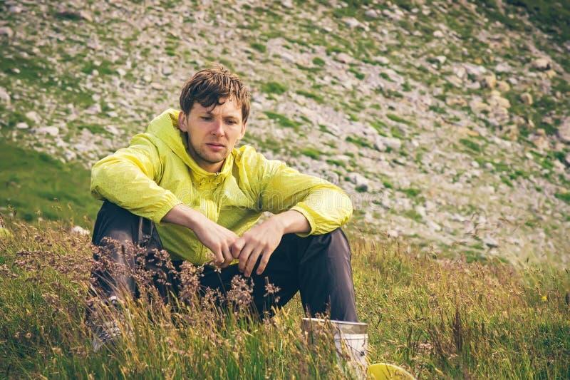 Mens het ontspannen in bergen die bij grasvallei de Reizende wandeling zitten royalty-vrije stock afbeeldingen
