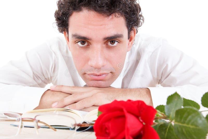 Mens het ontspannen met bloem en goed boek met glazen opzij stock foto's