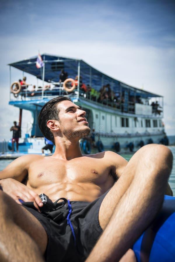 Mens het ontspannen op een vlot met actiecamera stock foto's