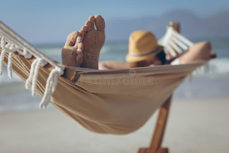 Mens het ontspannen op hangmat bij strand stock foto