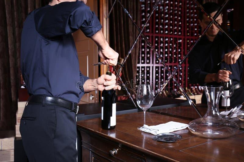 Mens het openen fles wijn royalty-vrije stock afbeelding