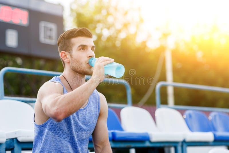 Mens in het overhemds drinkwater van de de zomersport bij straatstadion royalty-vrije stock fotografie