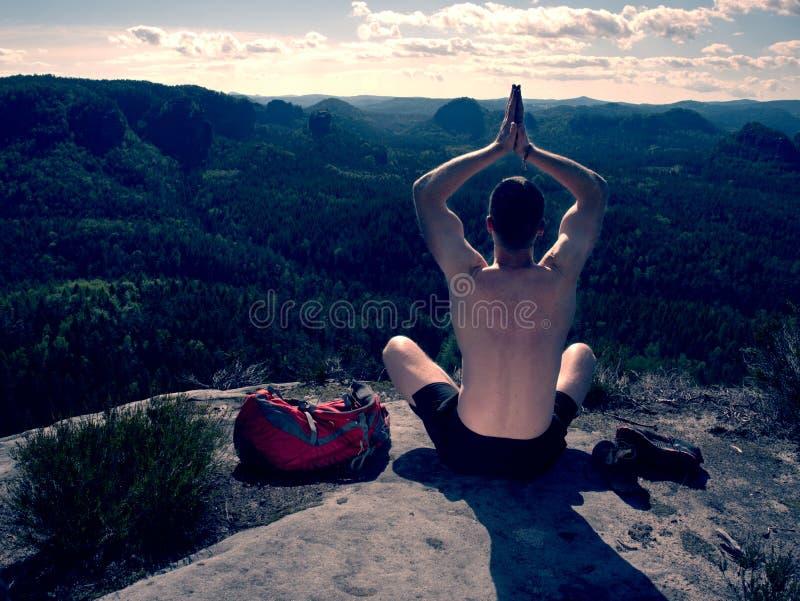 Mens het praktizeren yoga en meditatie op middelbare leeftijd in bergen royalty-vrije stock afbeelding