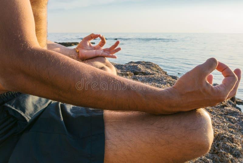 Mens het praktizeren yoga op het strand royalty-vrije stock afbeelding