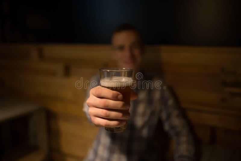 Mens het roosteren met ambachtbier in een bar stock foto