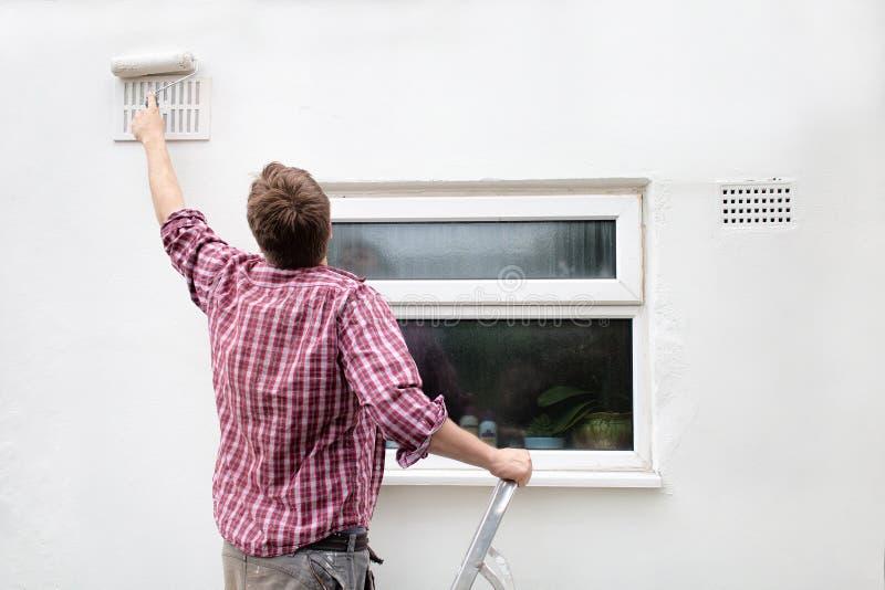 Mens het schilderen huismuur DIY-het huisverbetering stock fotografie