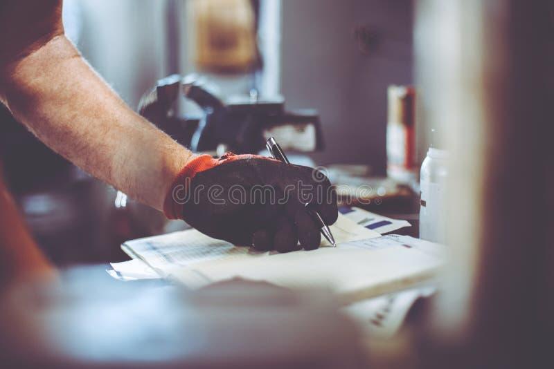 Mens het schrijven verplichtingen in zijn nota's royalty-vrije stock afbeeldingen
