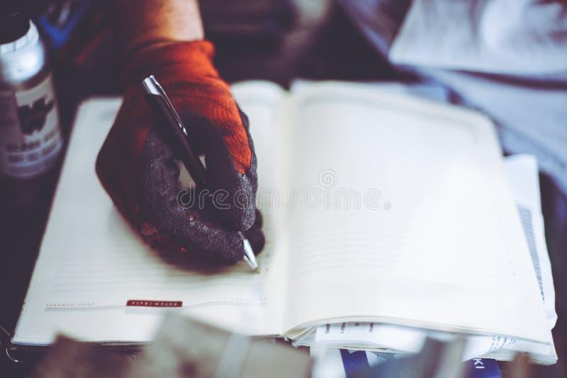 Mens het schrijven verplichtingen in zijn nota's royalty-vrije stock afbeelding
