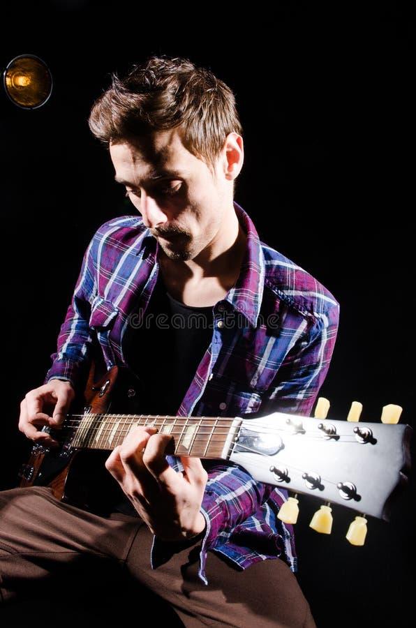 Mens het spelen gitaar in donkere ruimte stock foto