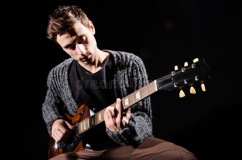 Mens het spelen gitaar in donkere ruimte royalty-vrije stock foto's