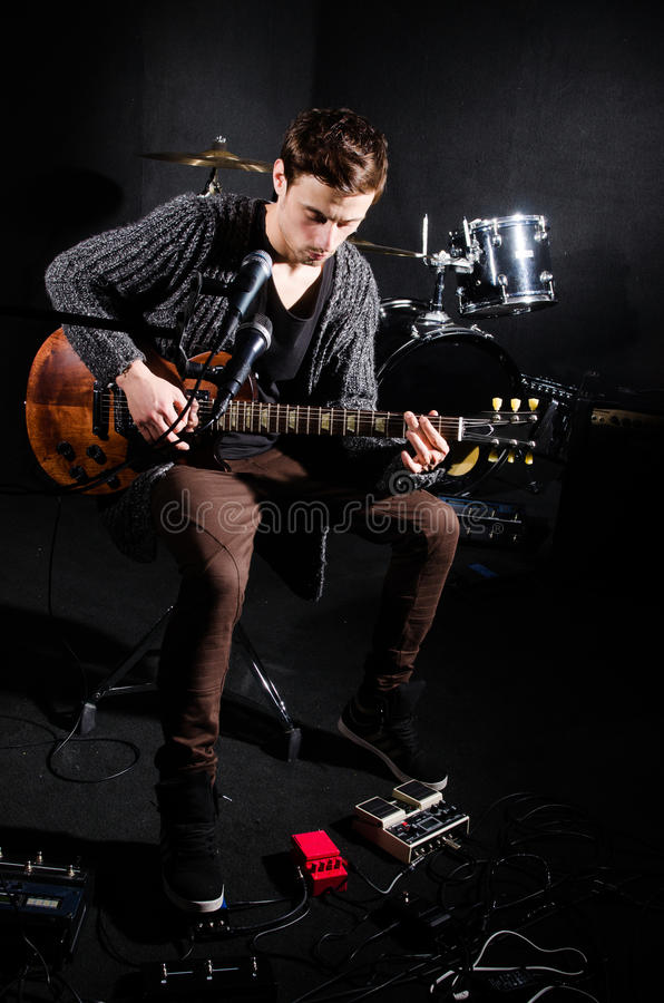 Mens het spelen gitaar in donkere ruimte stock fotografie