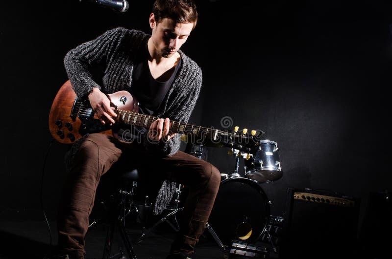 Mens het spelen gitaar in donkere ruimte royalty-vrije stock foto
