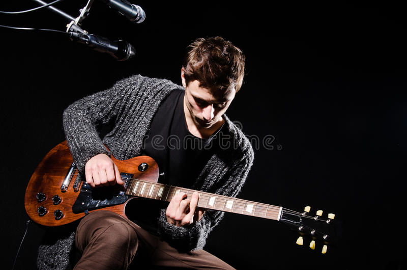 Mens het spelen gitaar in donkere ruimte stock afbeelding