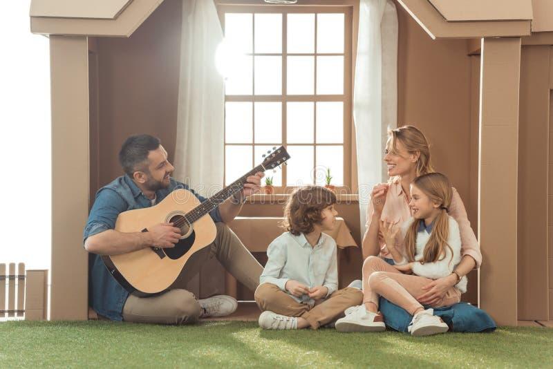 mens het spelen gitaar voor zijn familie bij nieuw stock foto
