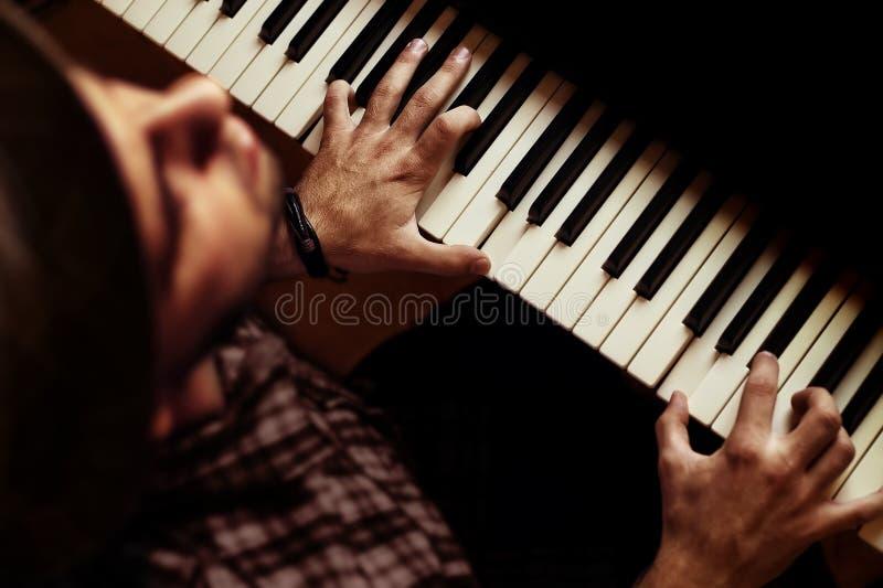 Mens het spelen op piano op dramatisch donker stadium royalty-vrije stock afbeeldingen