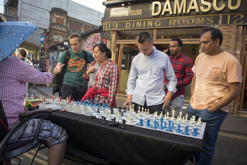 Mens het spelen schaak met passers langs in Baksteensteeg, Londen De straat is het hart van de gemeenschap van Londen ` s inwoner royalty-vrije stock fotografie