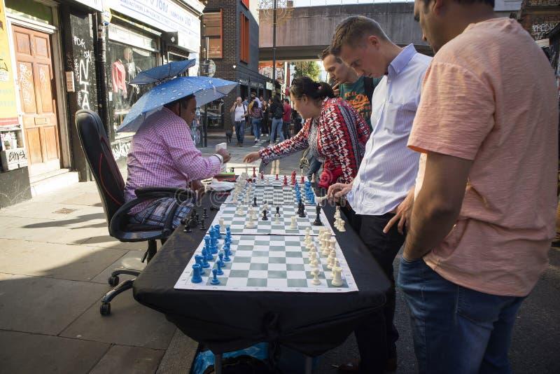 Mens het spelen schaak met passers langs in Baksteensteeg, Londen De straat is het hart van de gemeenschap van Londen ` s inwoner royalty-vrije stock foto's