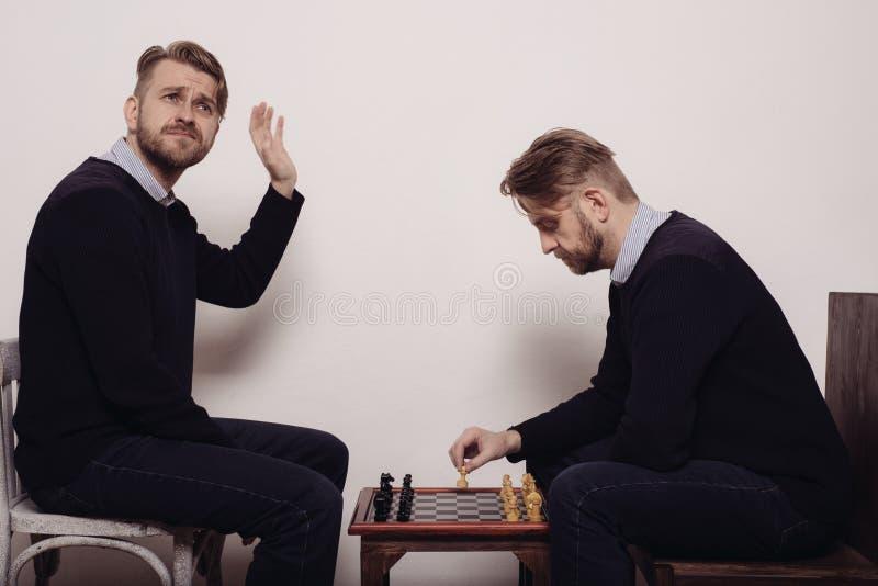 Mens het spelen schaak tegen zich schot in de studio royalty-vrije stock foto's