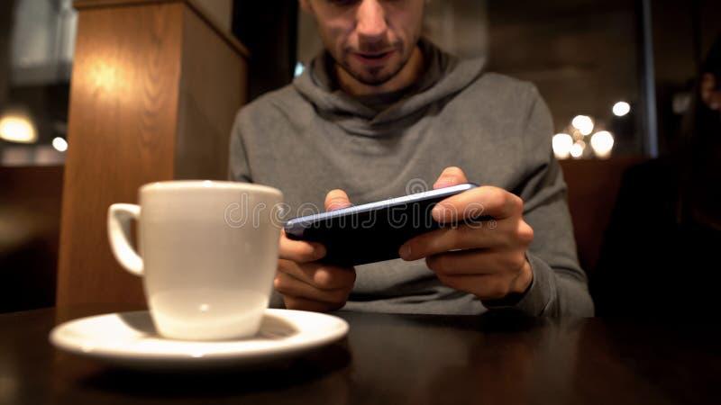 Mens het spelen videospelletje in koffie, gadgetverslaving, uitstelprobleem stock foto
